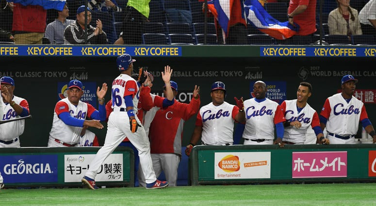 Outfielder Yoelkis Cespedes #16 of Cuba high fives with his teammates after scoring a run in the 2017 World Baseball Classic Tokyo, Japan – Mar. 8