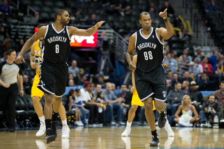 Jason Collins of the Nets celebrates after making a basket with teammate Alan Anderson #6 during a game against the Denver Nuggets at Pepsi Center on February 27, 2014 in Denver, Colorado.