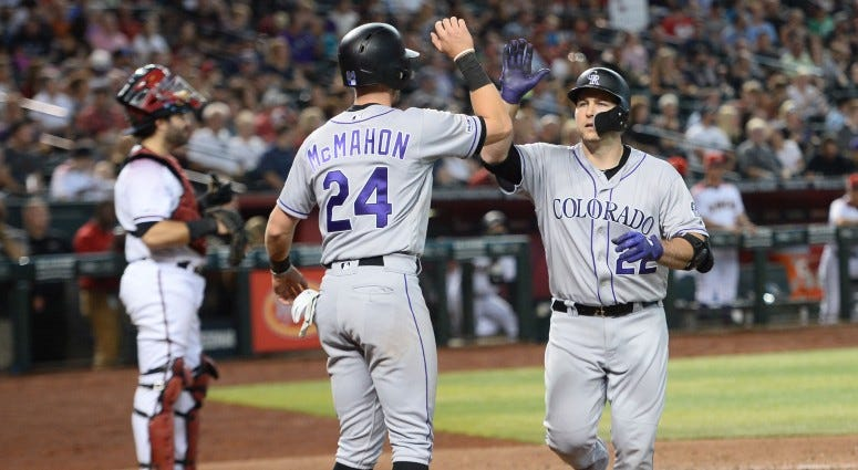 Colorado Rockies pinch hitter Chris Iannetta (22) slaps hands with Colorado Rockies second baseman Ryan McMahon (24) after hitting a two-run home run against the Arizona Diamondbacks during the eighth inning on Jul 7, 2019 at Chase Field.