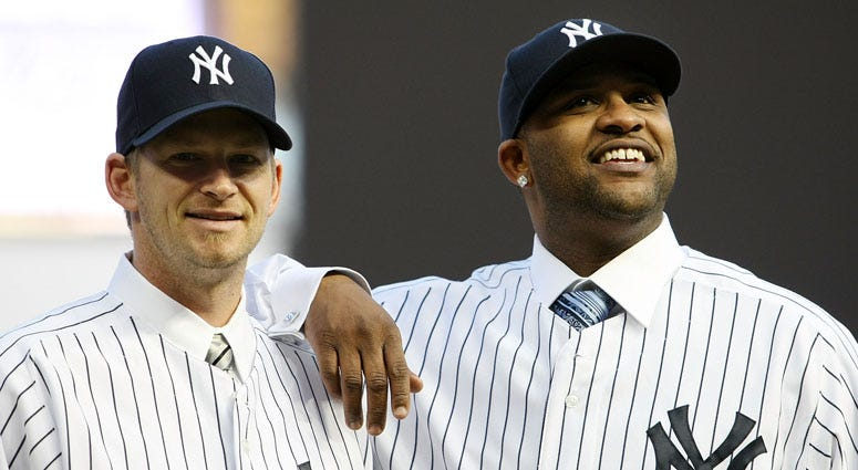CC Sabathia and A.J. Burnett pose for photographers after a press conference announcing their signings with the Yankees on Dec. 18, 2008.