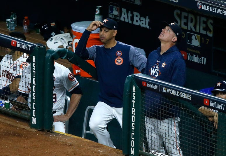 Bench coach Alex Cora and manager A.J. Hinch of the Astros look on from the dugout during the fifth inning against the Los Angeles Dodgers in game five of the 2017 World Series at Minute Maid Park on October 29, 2017 in Houston, Texas.