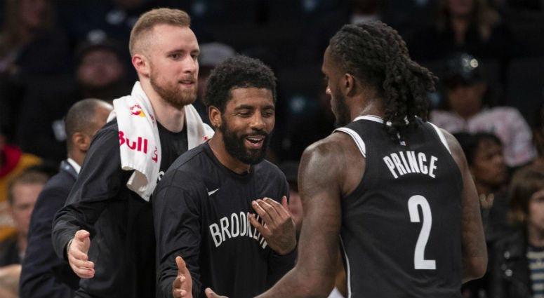 Brooklyn Nets guard Dzanan Musa, left, and /guard Kyrie Irving, center, greet forward Taurean Prince (2) as he comes into the bench during a timeout in the first half of an exhibition NBA basketball game against the Sesi/Franca Basketball Club, Friday, Oc