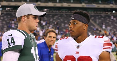 Saquon Barkley and Sam Darnold talk after a Jets-Giants game.