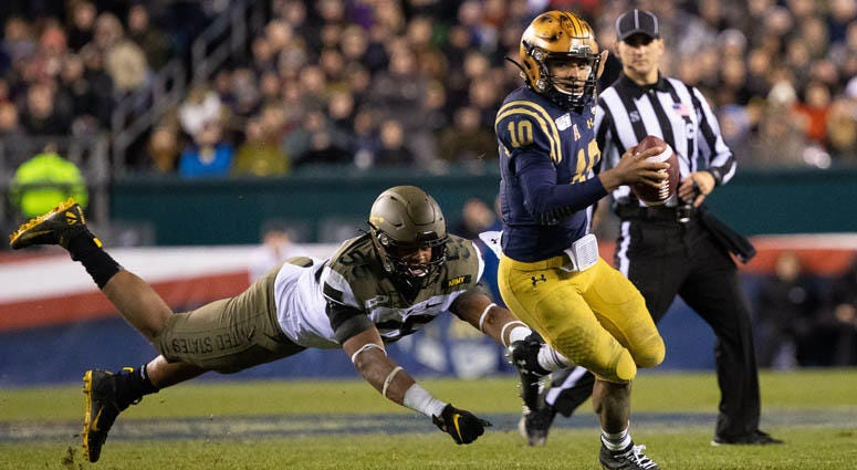 Navy quarterback Malcolm Perry runs with the ball past Army Black Knights defensive lineman Edriece Patterson on Dec. 14, 2019, at Lincoln Financial Field in Philadelphia.
