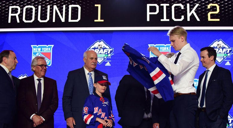 Kaapo Kakko puts on a team jersey after being selected as the No. 2 overall pick to the New York Rangers in the first round of the 2019 NHL Draft on June 21, 2019, at Rogers Arena in Vancouver, British Columbia.