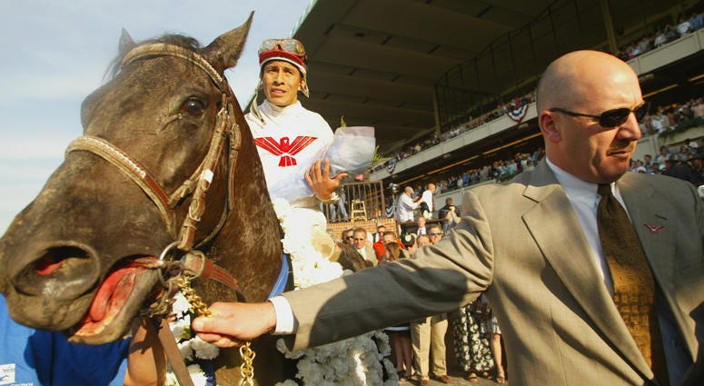 Sarava with jockey Edgar Prado is led to the winners' circle by trainer Kenneth McPeek after winning the 134th Belmont Stakes at Belmont Race Park on June 8, 2002.