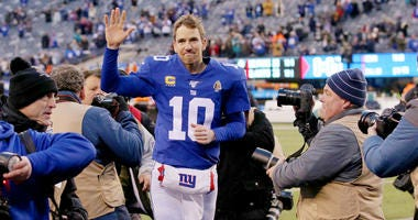 New York Giants quarterback Eli Manning (10) runs off the field after defeating the Miami Dolphins at MetLife Stadium