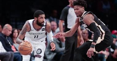 Nets guard Kyrie Irving dribbles as Atlanta Hawks forward Cam Reddish (22) defends on Jan. 12, 2020, at Barclays Center.