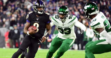 Ravens quarterback Lamar Jackson runs with the ball against the New York Jets on Dec. 12, 2019, at M&T Bank Stadium in Baltimore.
