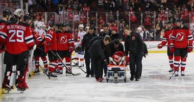 Feb 27, 2019; Newark, NJ, USA; Mirco Mueller (25) is rolled off the ice on a gurney after suffering an apparent injury during the third period against the Calgary Flames at Prudential Center. Mandatory Credit: Ed Mulholland-USA TODAY Sports