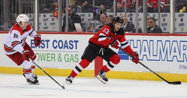 Devils center Nico Hischier skates with the puck past Hurricanes left wing Teuvo Teravainen on Feb. 10, 2019, at the Prudential Center.