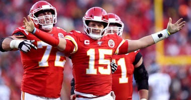 Patrick Mahomes of the Chiefs reacts with teammates Eric Fisher and Mitchell Schwartz after a fourth quarter touchdown pass against the Tennessee Titans in the AFC Championship Game at Arrowhead Stadium on January 19, 2020 in Kansas City, Missouri.
