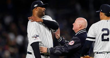 Yankees pitcher CC Sabathia reacts as he's examined by trainer Steve Donohue on Oct. 17, 2019, at Yankee Stadium.