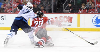 Oct 4, 2019; Newark, NJ, USA; New Jersey Devils center Blake Coleman (20) scores a goal while being checked by Winnipeg Jets defenseman Dmitry Kulikov (7) during the second period at Prudential Center.