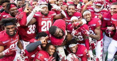 Temple players celebrate following their 24-17 win in overtime against Cincinnati in an NCAA college football against Cincinnati, Saturday, Oct. 20, 2018, in Philadelphia.