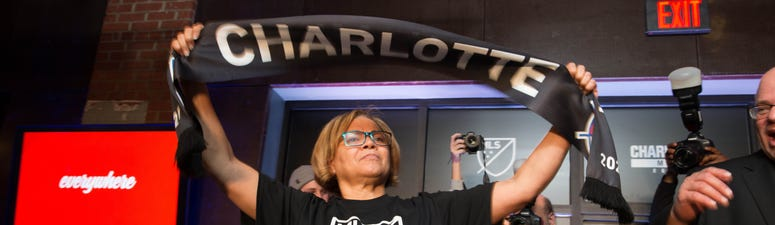 Charlotte mayor Vi Lyles holds up a Charlotte MLS scarf