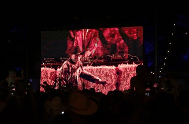 A large crowd dances in front of a screen when Diplo brings out Lil Nas X and Billy Ray Cyrus