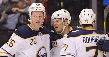 Rasmus Dahlin, Kyle Okposo and Evan Rodrigues