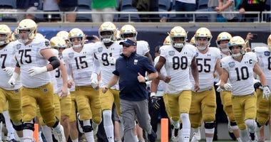 Notre Dame head coach Brian Kelly, center, runs onto the field with his players before the Camping World Bowl NCAA college football game against Iowa State in Orlando, Fla.
