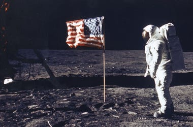 Edwin E. Aldrin Jr. poses on the moon next to the American flag.