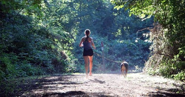 A jogger and her dog run through the woods on July 12, 2018 in Bethpage, New York.