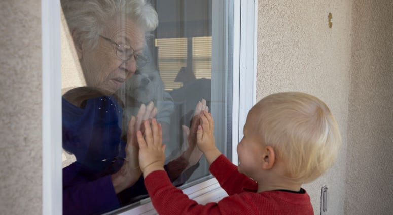 Mary-Lou McCullagh, 83, and her husband Bob, 84, greet Axel Stirton, 2, the little boy who lives across the street April 3, 2020 in Ventura, California.