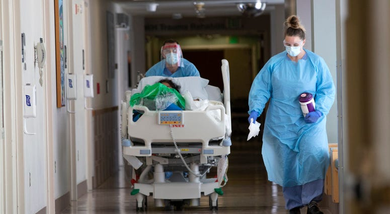 A nurse on infection control accompanies a patient being transferred from the ICU COVID unit to the acute care COVID unit at Harborview Medical Center on May 7, 2020 in Seattle, Washington.