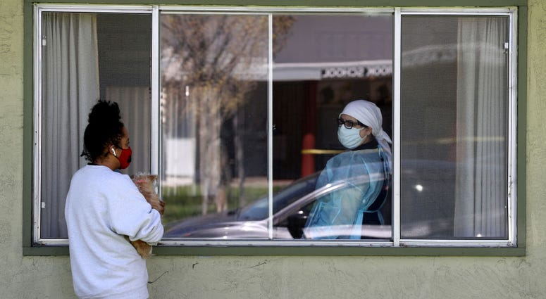 Adrina Rodriguez (L) talks with a nurse through a window as she visits her father who is a patient at the Gateway Care and Rehabilitation Center that has tested negative for COVID-19 on April 14, 2020 in Hayward, California.
