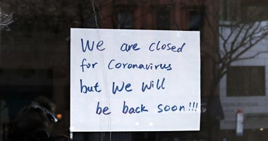 : A sign in a restaurant window reads 'we are closed for coronavirus but we will be back soon!!!' during the COVID-19 pandemic on April 21, 2020 in New York City.
