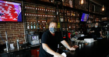Zack Vermes a bartender at Carmines Ybor Italian restaurant wipes off the bar while awaiting patrons on June 26, 2020 in Tampa, Florida.
