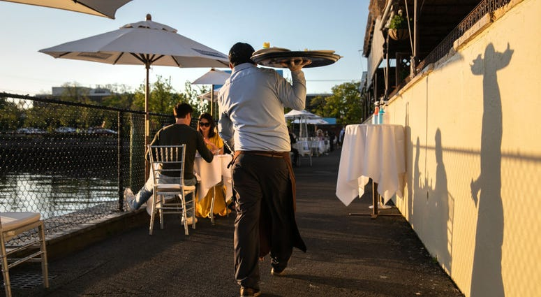 : A waiter serves patrons at L'escale restaurant on May 20, 2020 in Greenwich, Connecticut.