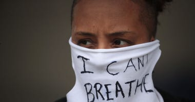 "A person wears a mask that reads ""I CAN'T BREATHE"" as demonstrators continue to protest the death of George Floyd following a night of rioting on May 29, 2020 in Minneapolis, Minnesota."