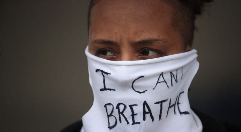 """A person wears a mask that reads """"I CAN'T BREATHE"""" as demonstrators continue to protest the death of George Floyd following a night of rioting on May 29, 2020 in Minneapolis, Minnesota."""