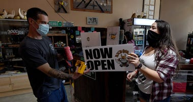 "LAS VEGAS, NEVADA - MAY 29: Frank Pravatta (L) and Michaela Douglas get ready to put ""Now open"" signs outside Axehole Vegas inside Neonopolis as the indoor axe-throwing range and bar opens for the first time since closing in Marc"