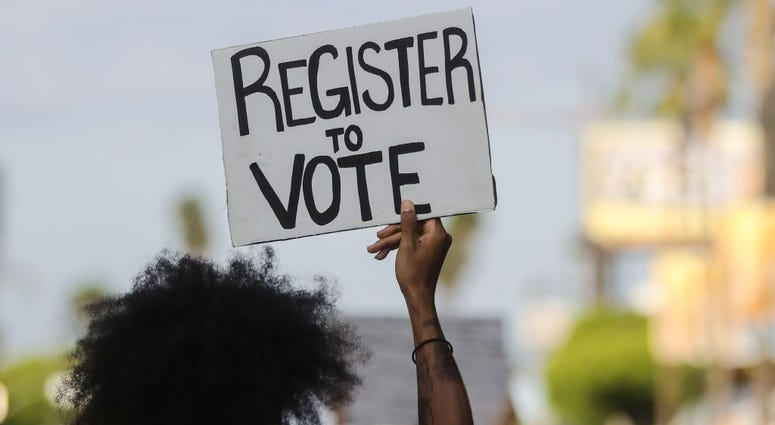A protester carries a 'Register to Vote' sign during a peaceful demonstration against racism and police brutality on June 06, 2020 in Los Angeles, California