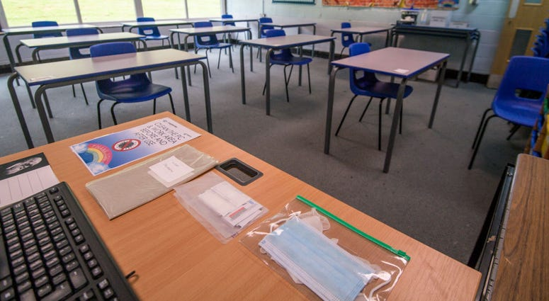 Spare face masks are seen on a teachers desk as a classroom is set out for social distancing at Longdendale High School on July 16, 2020 in Hyde, England