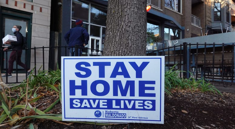 A sign along the sidewalk in an area lined with bars and restaurants in the Wicker Park neighborhood encourages people to stay home on November 11, 2020 in Chicago, Illinois.