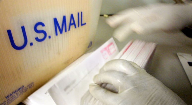 A corporate mailroom employee uses gloves while sifting through letters October 15, 2001 in New York City.