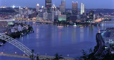 View of the downtown Pittsburgh skyline at dusk, showing the Allegheny and Monongahela rivers joining to form the Ohio River.