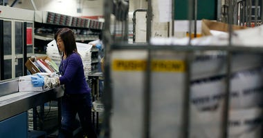 An United States Postal Office employee puts a bundle of mail onto a machine at the Processing and Distribution Center on December 16, 2013 in San Francisco, California