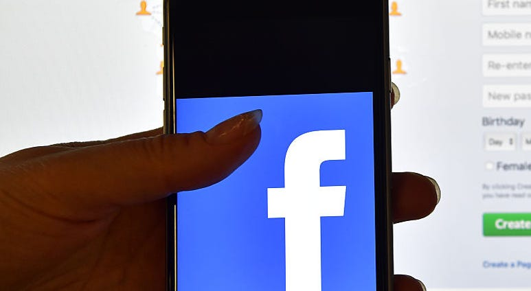 LONDON, ENGLAND - AUGUST 03: A person holds an iPhone displaying the Facebook app logo in front of a computer screen showing the facebook login page on August 3, 2016 in London, England.