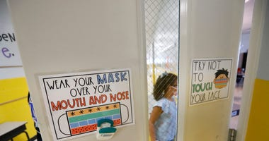 Students return to their classrooms as signage guides proper use of mandated face masks for first and second graders in the hallway at Millington Elementary School on the first day of class Monday, August 10, 2020. Millington 3