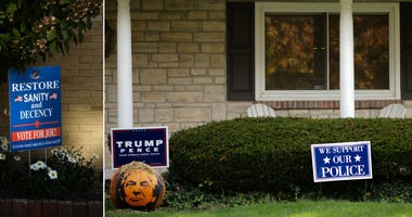 On the left, signs in support of Democratic presidential candidate and former vice president Joe Biden sit outside the Yoss Law Office on Friday, Oct. 9, 2020 in Woodsfield, Ohio.