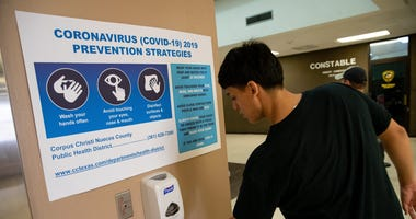 A man uses hand sanitizer underneath a coronavirus prevention sign at the entrance of the Nueces County Courthouse on Friday, March 13, 2020. Covid 19 Corpus 6
