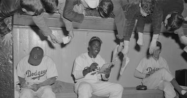Jackie Robinson and teammates signing autographs for fans in 1949