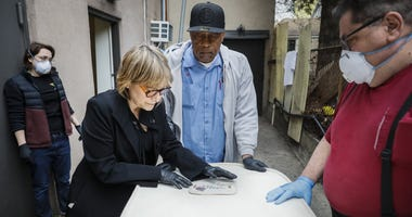 Funeral director Amy Cunningham, of Fitting Tribute Funerals, center left, pins an embroidered nameplate to the casket of Winifred Pardo at Sherman's Flatbush Memorial Chapel, Wednesday, April 29, 2020, in the Brooklyn borough of New York.