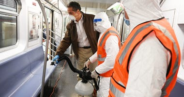 Cuomo disinfects a 7 train car in Queens