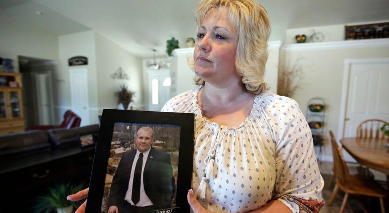 FILE - In this July 13, 2016 file photo, Laurie Holt holds a photograph of her son Josh Holt at her home, in Riverton, Utah.