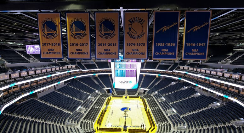 In this Aug. 26, 2019, file photo, the Golden State Warriors championship banners hang above the seating and basketball court at the Chase Center in San Francisco. The Warriors will play the Brooklyn Nets at home Thursday night, March 12, 2020