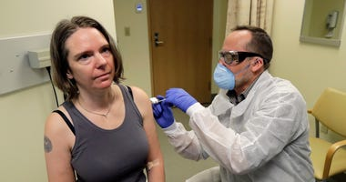pharmacist gives Jennifer Haller, left, the first shot in the first-stage coronavirus test